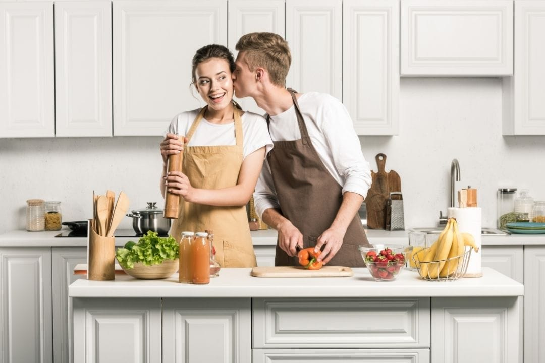 girl cooking in a bright kitchen with her boyfriend