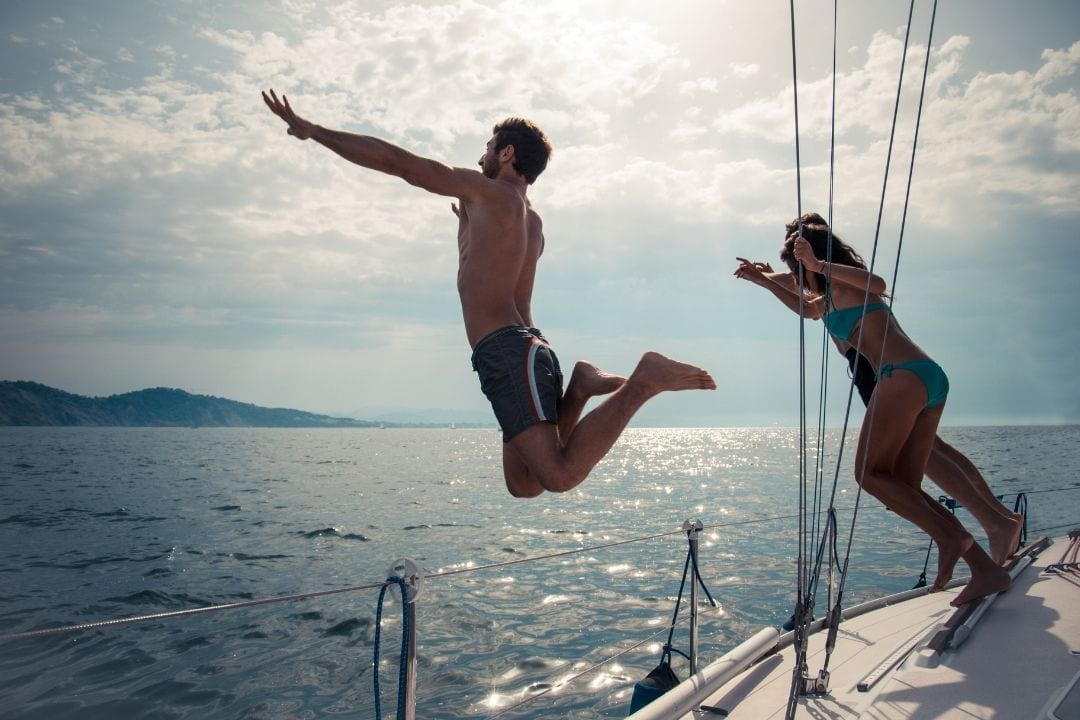 people jumping from a sailboat