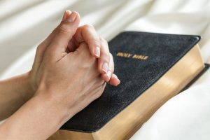 hands praying on a bible