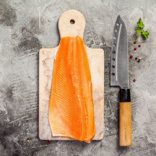 chef knife next to a salmon fillet